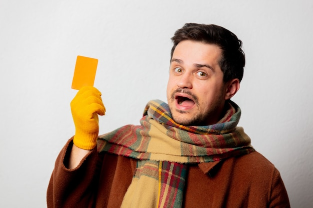 Style man in coat and scarf with card