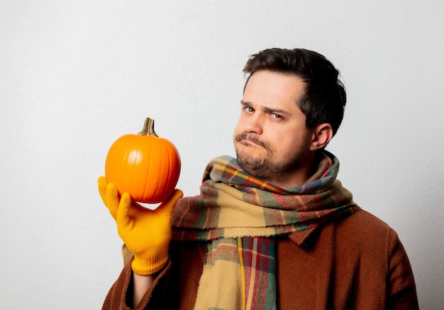 Style man in coat and scarf with pumpkin