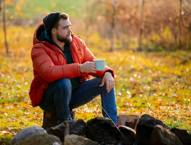 Style man in down jacket with cup of coffee sitting near bonfire