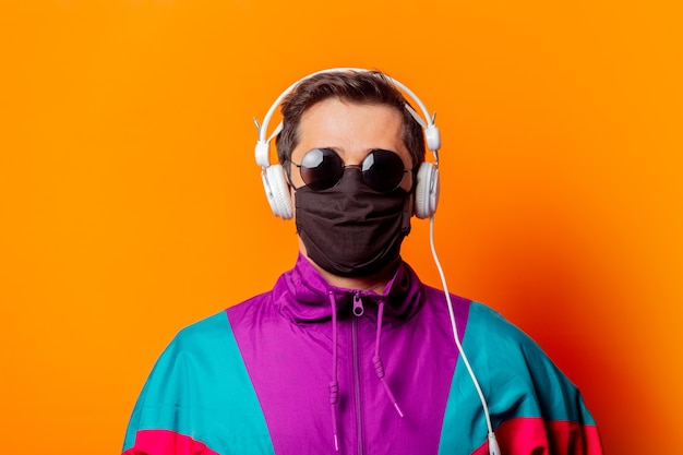 Style man in face mask and 80s tracksuit with headphones