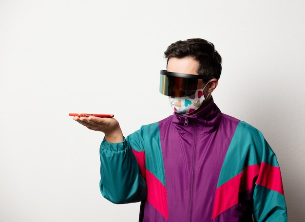Style man in tracksuit and sunglasses with mobile phone Premium Photo