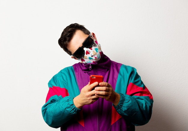 Style man in tracksuit and sunglasses with mobile phone
