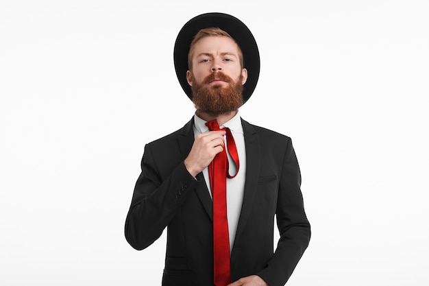 Style, men's wear and fashion concept. picture of fashionable caucasian male with thick ginger beard getting dressed for some official event, wearing black hat and suit, knotting red elegant tie