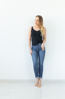 Style, people concept - young woman in jeans and black shirt standing over the white wall
