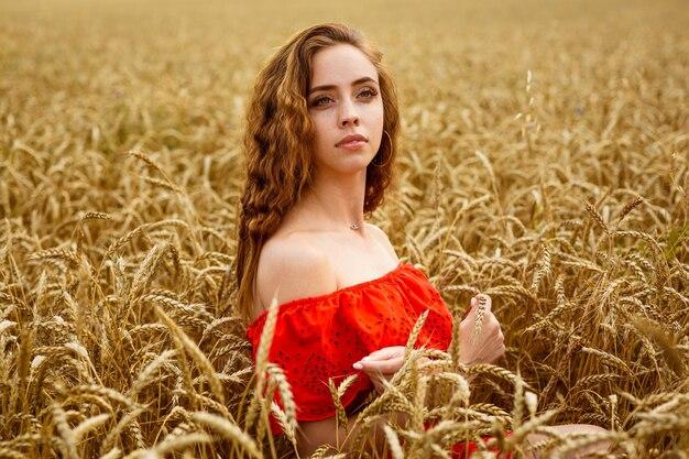 赤い服を着たスタイルの赤毛の女の子は、美しさの黄色い麦畑白人の本物の女の子の肖像画にとどまります...