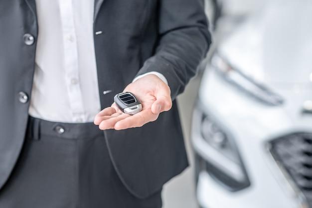 Стиль. стильный автомобильный брелок лежит на вытянутой ладони мужчины в темном деловом костюме, лица не видно