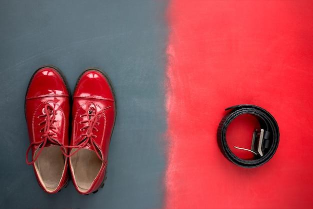 スタイル。古典的な赤いパテントレザーの靴と赤と灰色の背景にズボンの黒革のベルトの平面図です。