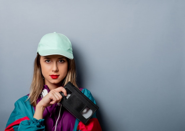 Style woman in 90s clothes style with vhs video cassette