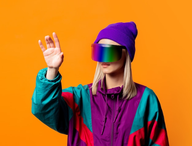 Style woman in 90s tracksuit with vr glasses on orange