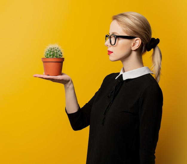 Style woman in black formal clothes with cactus