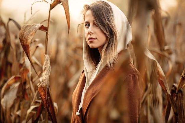 Style woman in coat on corn field in autumn time season