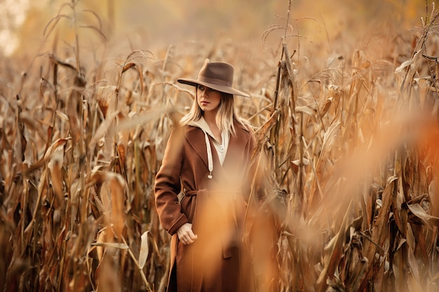 Style woman in coat and hat on corn field in autumn time season