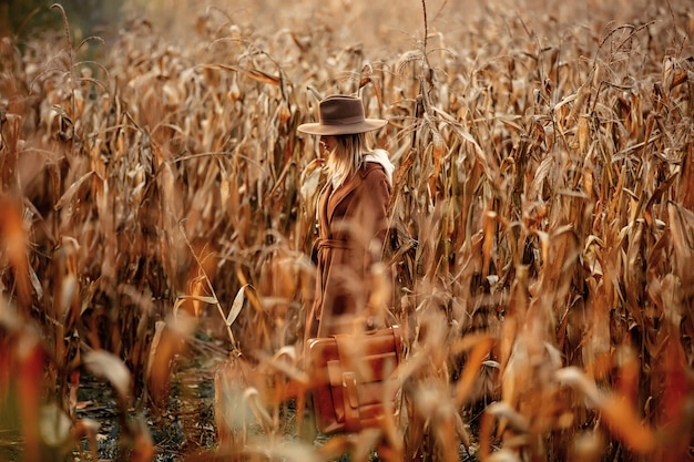 Style woman in coat and hat with travel suitcase on corn field in autumn time season