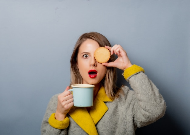 Style woman in coat with cup of coffee and cookie
