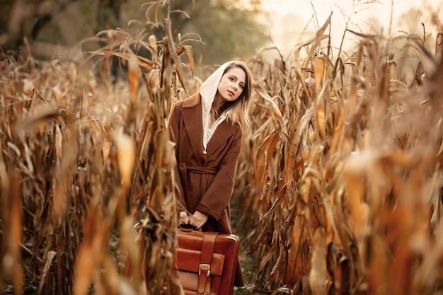 Style woman in coat with suitcase on corn field in autumn time season
