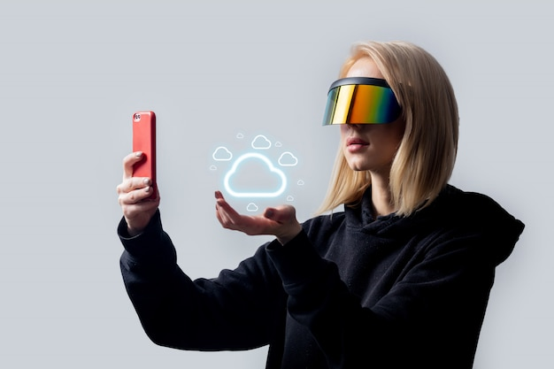 Style woman in concept vr glasses using cloud storage on mobile phone on white wall