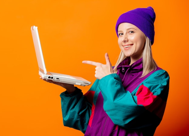 Женщина стиля в спортивном костюме 90-х с блокнотом на оранжевом