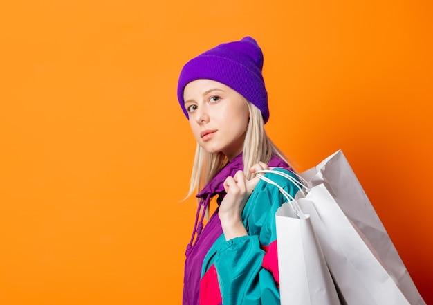 Женщина стиля в спортивном костюме 90-х с сумками на оранжевом