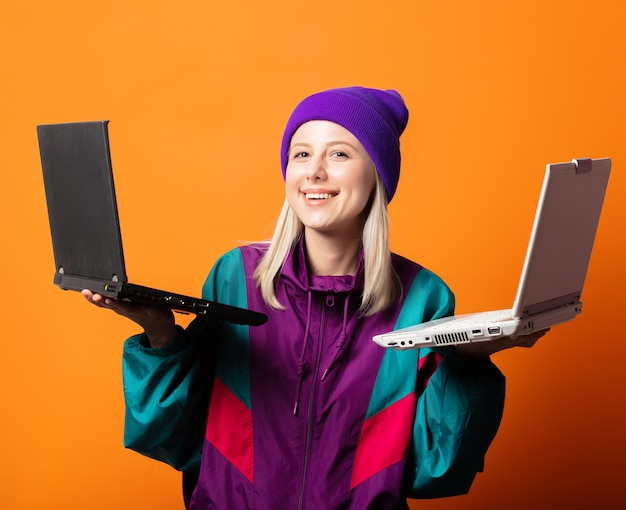 Стильная женщина в спортивном костюме 90-х с двумя блокнотами на оранжевом