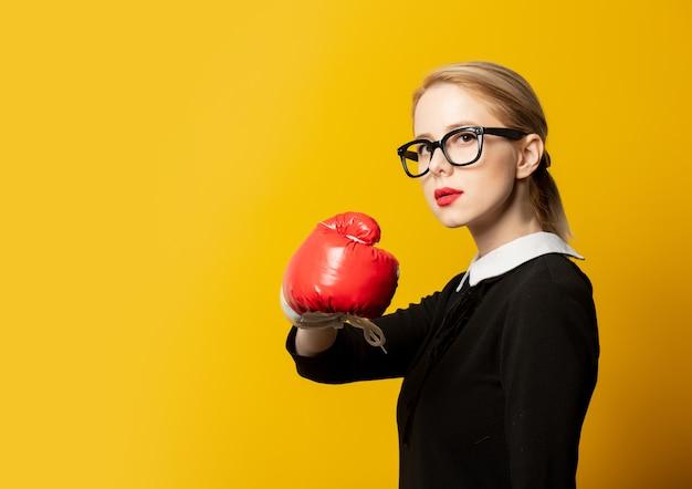Женщина стиля в черной формальной одежде с боксерской перчаткой