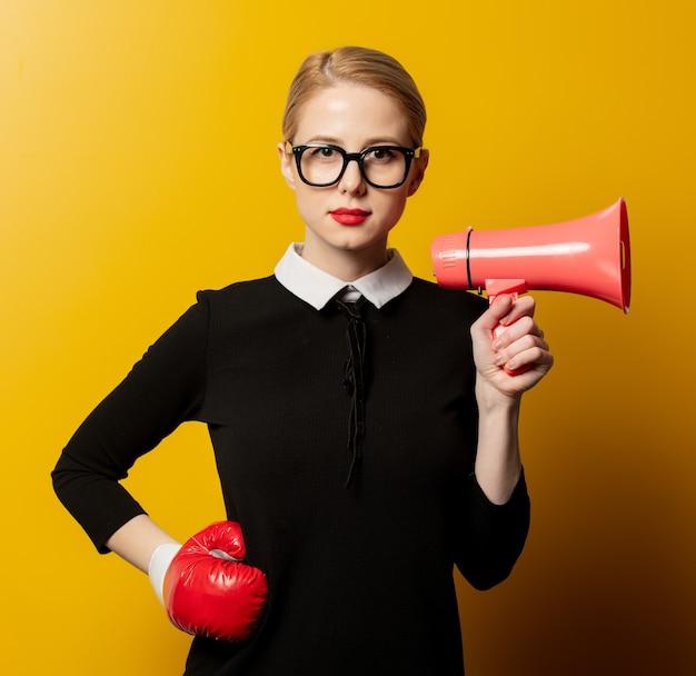 Стильная женщина в черной официальной одежде с мегафоном и боксерской перчаткой