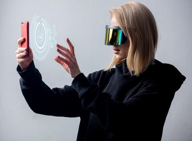 Стиль женщина в очках концепции vr, используя облачное хранилище на мобильном телефоне на белой стене