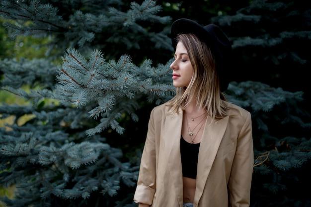 Стиль женщина в шляпе и куртке возле сосны