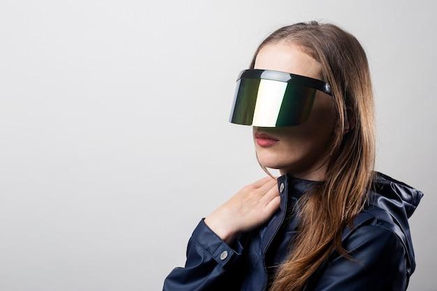 가상 현실 안경을 쓰고 밝은 배경에 파란색 재킷을 입은 스타일 여성.