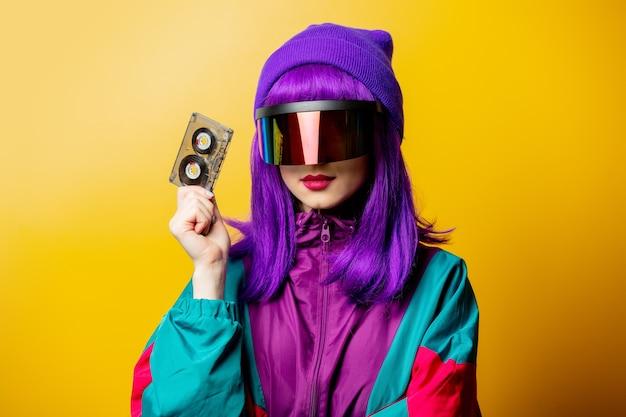 Стильная женщина в очках vr и спортивном костюме 80-х с аудиокассетой на желтой стене