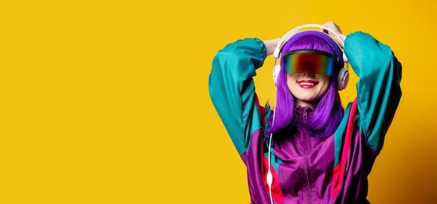 Женщина стиля в очках vr и спортивном костюме 80-х с наушниками на желтой стене