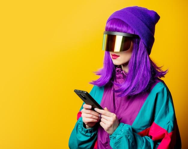 Стильная женщина в очках vr и спортивном костюме 80-х с мобильным телефоном на желтой стене