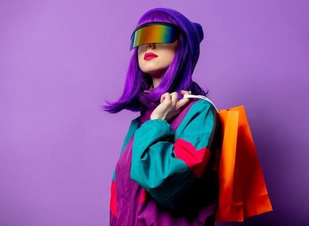 Стильная женщина в очках vr и спортивном костюме 80-х с сумками на фиолетовой стене