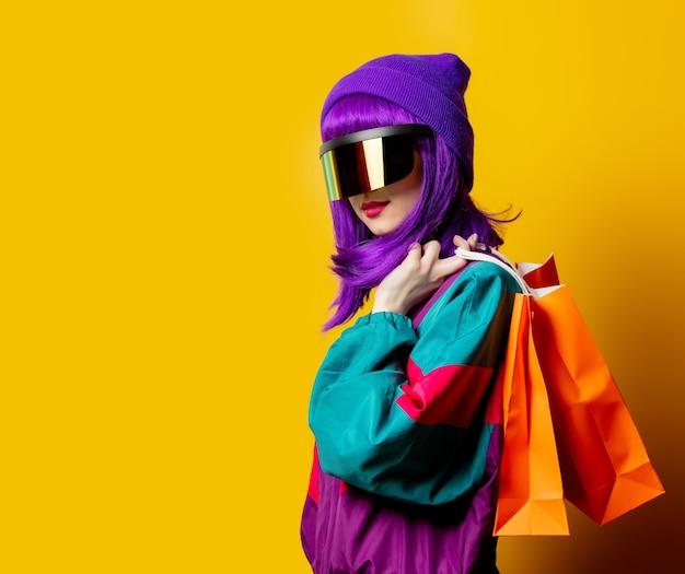 Стильная женщина в очках vr и спортивном костюме 80-х с сумками на желтой стене