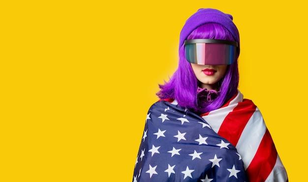Стильная женщина в очках vr и спортивном костюме 80-х с флагом сша на желтой стене
