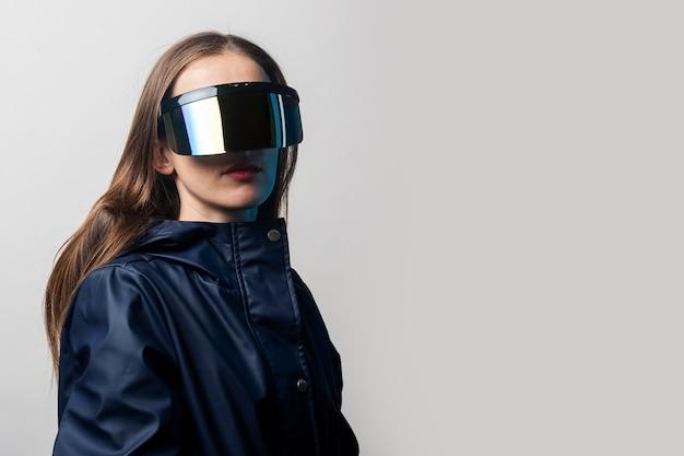 Vr 안경을 쓰고 밝은 배경에 파란색 재킷을 입은 스타일 여성.