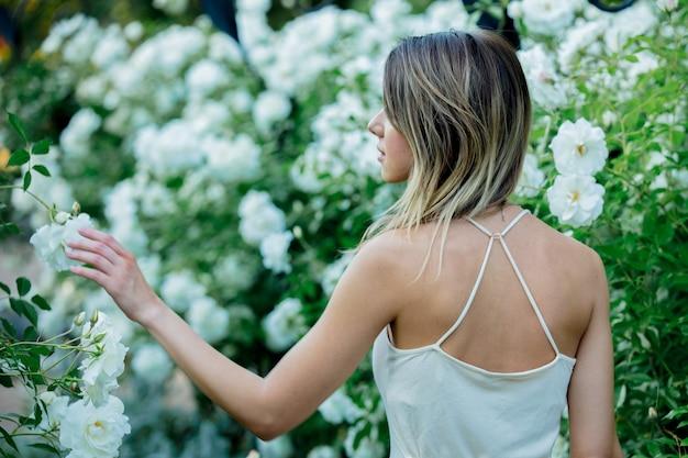 봄 시간에 정원에서 흰 장미 근처 스타일 여자