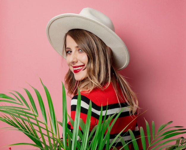 Style woman in striped sweater and hat on pink wall