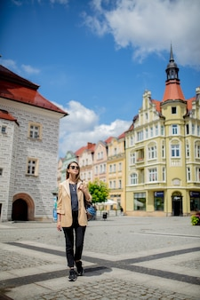 Style woman in sunglasses and backpack in aged city center square. poland