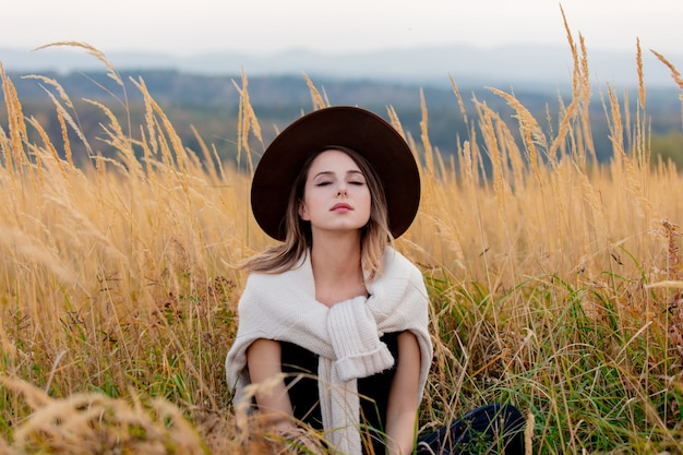 Style woman in sweater sits in yellow grass at countryside with mountains