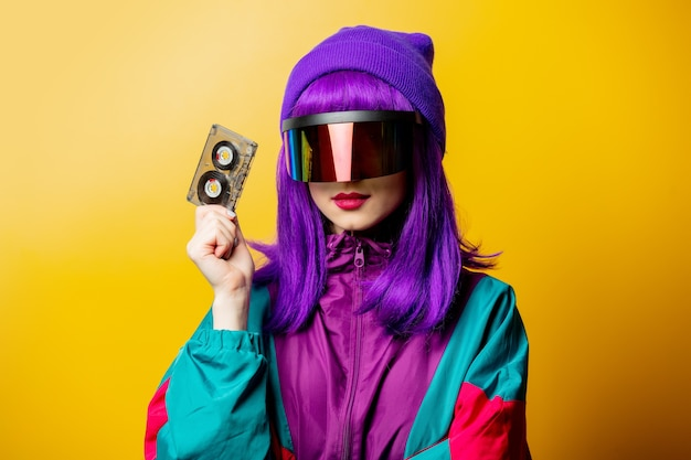 Style woman in vr glasses and 80s tracksuit with audio tape on yellow wall