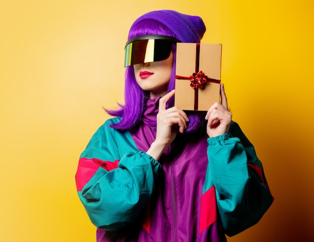 Style woman in vr glasses and 80s tracksuit with gift box on yellow wall