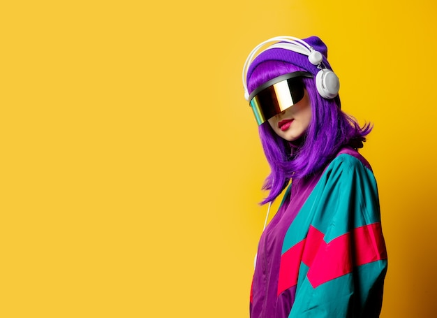 Style woman in vr glasses and 80s tracksuit with headphones on yellow wall