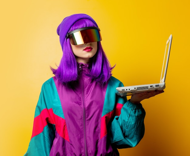 Style woman in vr glasses and 80s tracksuit with laptop on yellow wall
