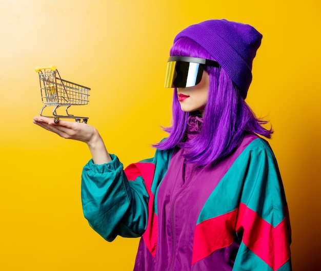 Style woman in vr glasses and 80s tracksuit with shoping cart on yellow wall