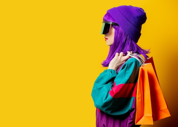 Style woman in vr glasses and 80s tracksuit with shopping bags on yellow wall