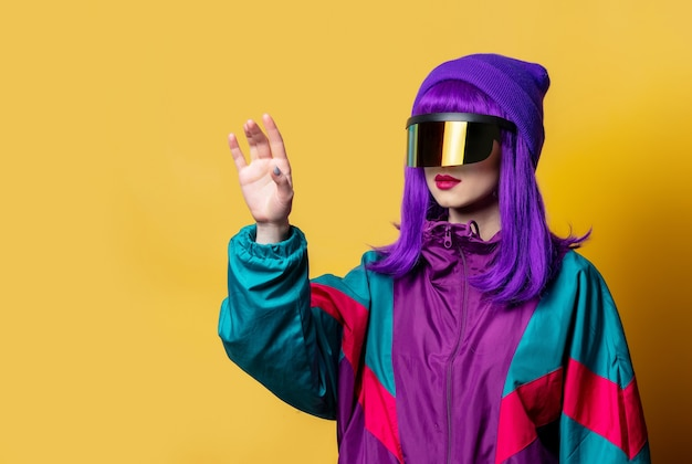 Style woman in vr glasses and 80s tracksuit on yellow wall