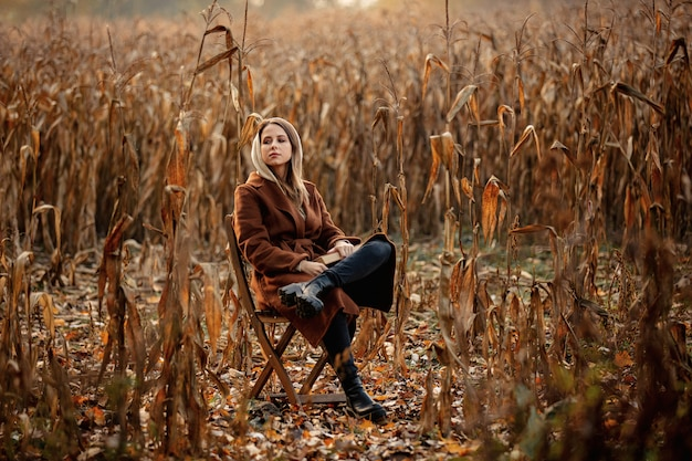 Style woman with book sitting on chair on corn field in autumn time season