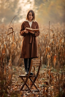 Style woman with book stay on chair on corn field in autumn time season