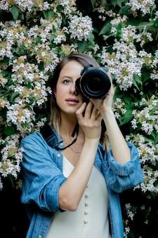 봄철 정원에 있는 꽃이 만발한 나무 근처에 카메라를 들고 있는 스타일 여자