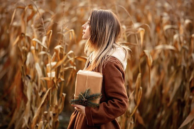 Style woman with gift box on corn field in autumn time season